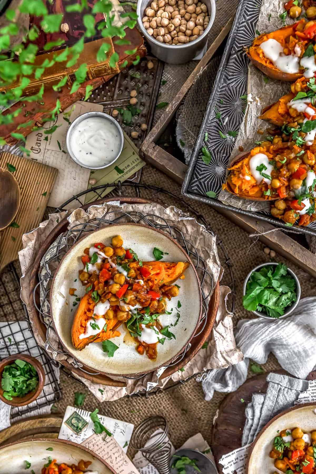 Tablescape of Moroccan Spiced Chickpeas and Garlic Sauce over sweet potatoes