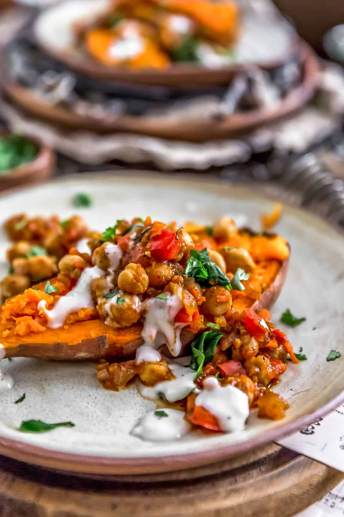 Plated Moroccan Spiced Chickpeas and Garlic Sauce over a sweet potato