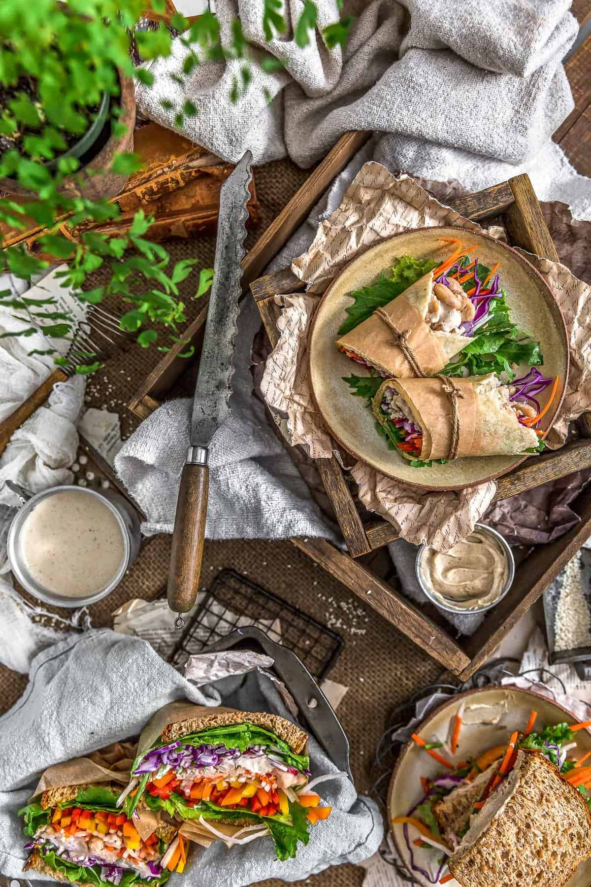 Tablescape of sandwiches and wraps with Vegan Tangy Honey Mustard Mayo