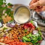 Vegan Creamy Caesar Dressing pouring over a salad