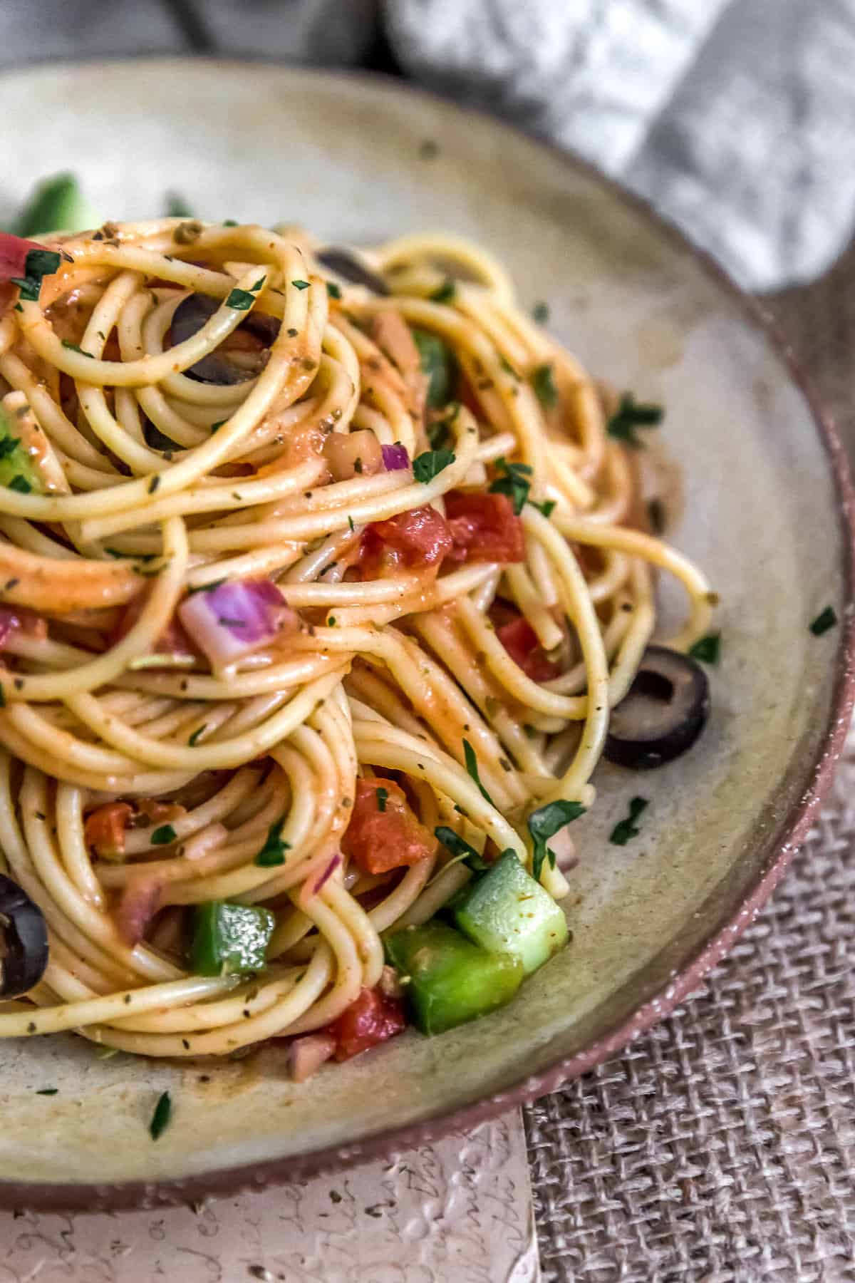 Healthy Italian Spaghetti Salad piled high on a plate