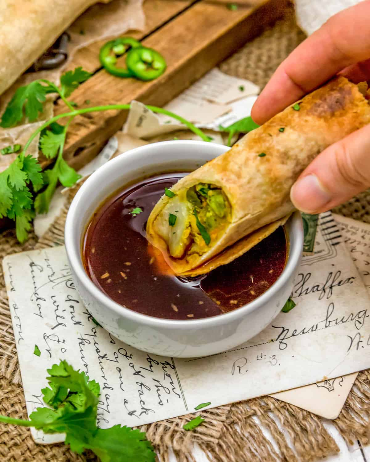 Dipping Vegan Samosa Roll in Sweet and Sour Sauce