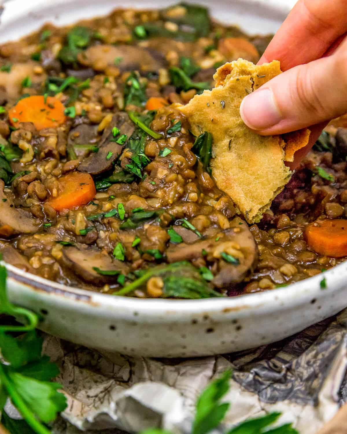 Dipping bread in French Lentil Rice Mushroom Stew