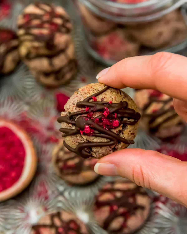 Holding a Vegan Chocolate Raspberry Cream Cookie